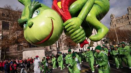 Balloon handlers hold Dr. Seuss' The Grinch close