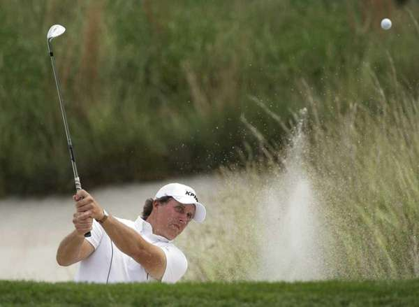 Phil Mickelson chips out of a bunker on
