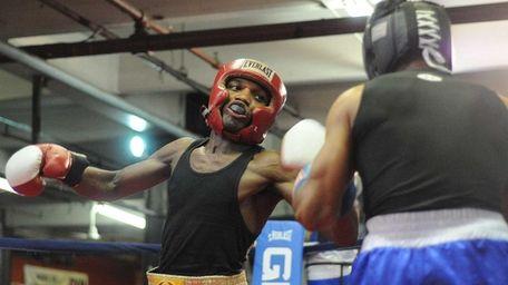 Titus Williams, 22 of Elmont, left, throws a