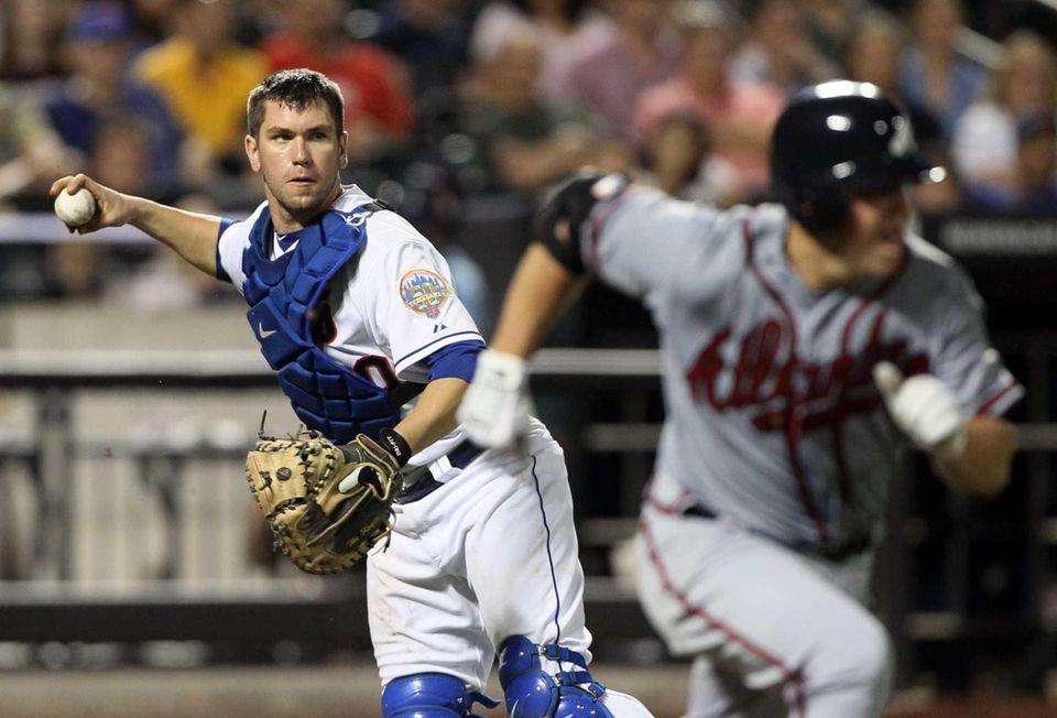 Josh Thole throws out pitcher Kris Medlen of