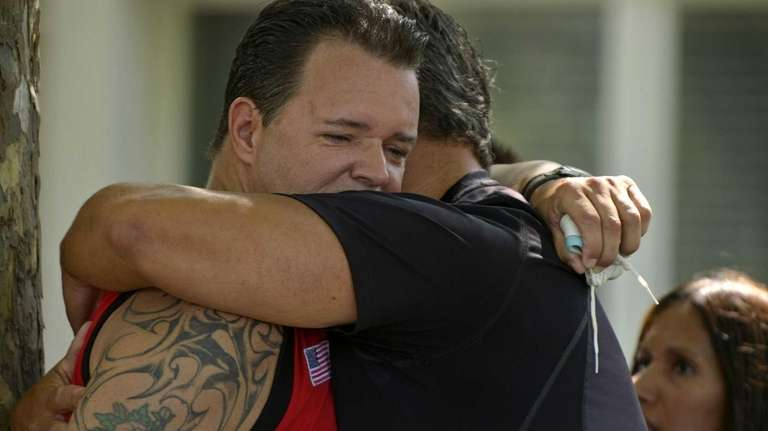 Greg Buckley Sr., left, is consoled outside his