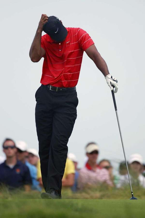Tiger Woods reacts to his tee shot on