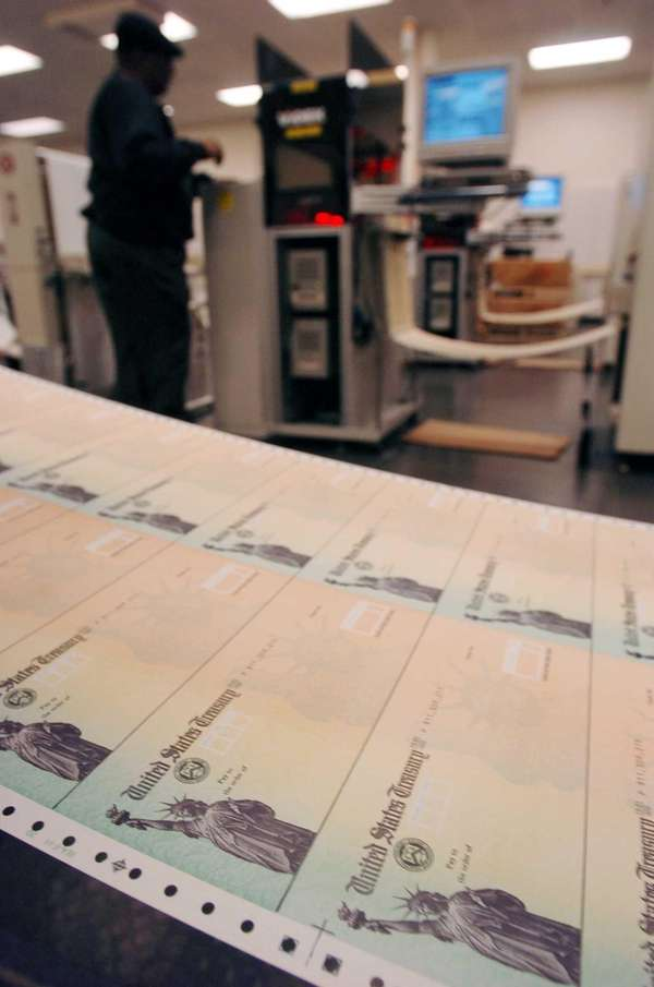 Rolls of blank social security checks run through