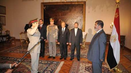 Egyptian President Mohammed Morsi, right, swears in newly-appointed