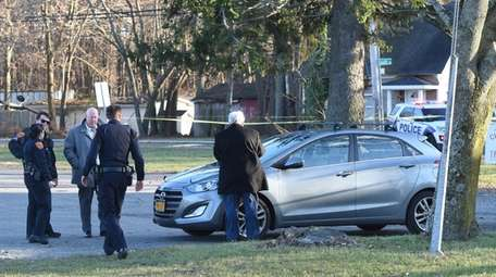 Investigators probe a vehicle in which a man