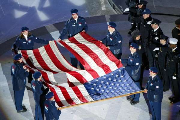 Olympians carry the tattered American flag from the