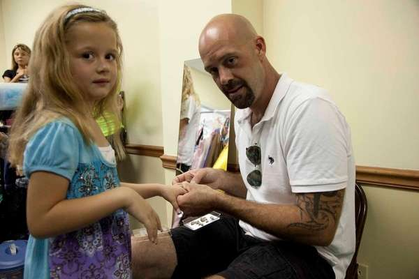 A father helps his daughter prepare for a