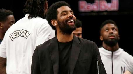Nets guard Kyrie Irving, center, jokes with forward
