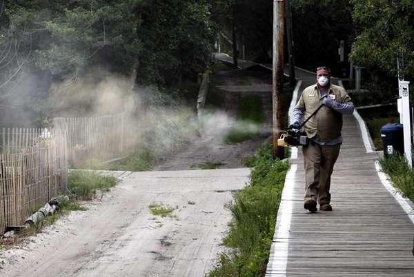 Suffolk County worker George Harned performs spraying along