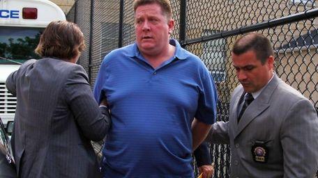 Raymond Roth is brought into Nassau police headquarters