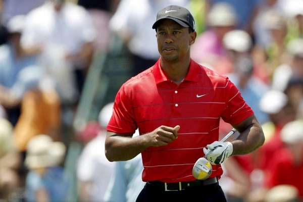 Tiger Woods walks down the first fairway during