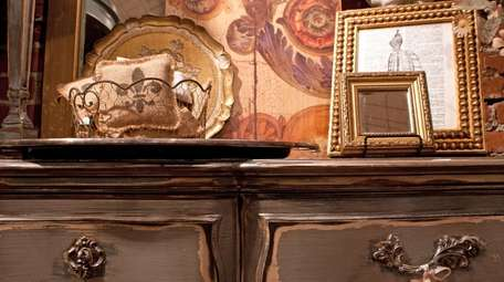 An antique dresser with French décor accents.