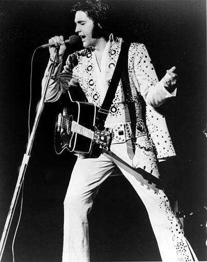 Elvis Presley performs in his iconic white jumpsuit.