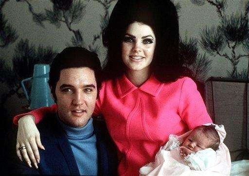 Elvis Presley poses with wife, Priscilla, and daughter