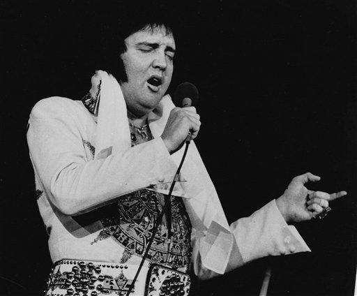 Elvis Presley, wearing his white jumpsuit, performs on