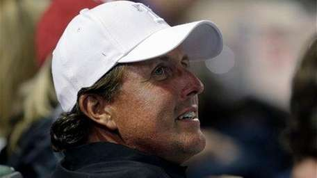 Phil Mickelson watches a baseball game between the