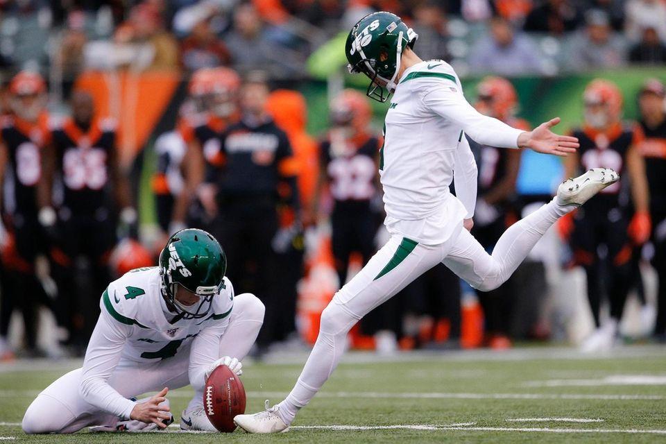 Jets kicker Sam Ficken, right, boots a field