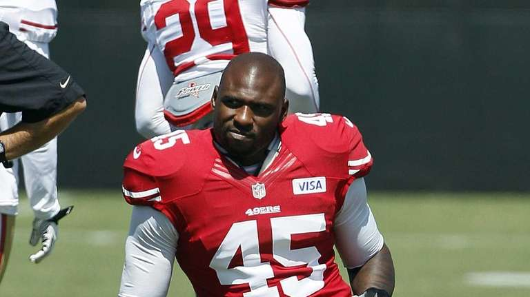 San Francisco 49ers running back Brandon Jacobs kneels