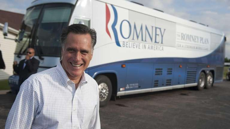 Mitt Romney stands in front of his campaign