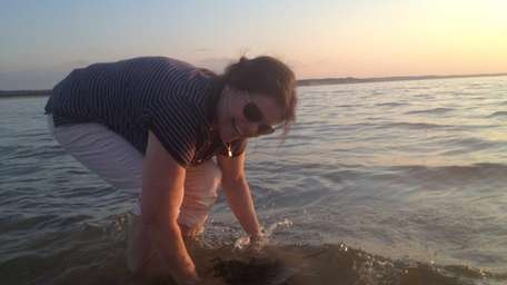 Stephanie Mitchell, 58, places a beached rock covered