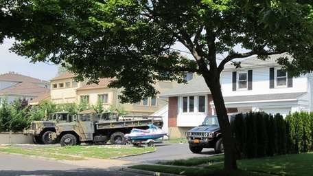 Three salvaged military trucks occupy a front yard