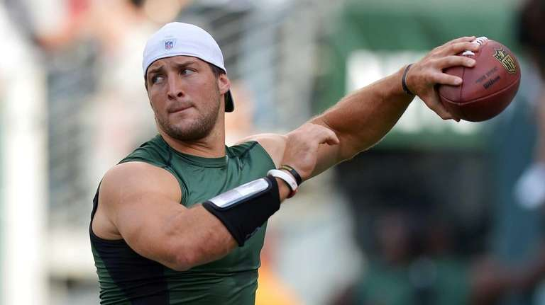 Tim Tebow warms up before the game against