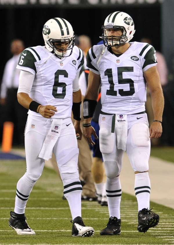 Mark Sanchez, left, meets teammate Tim Tebow after