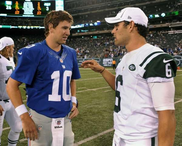 Giants quarterback Eli Manning, left, speaks with Jets