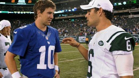 Giants quarterback Eli Manning, left, speaks with Jets