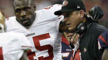 Brandon Jacobs is helped off by coach Jim