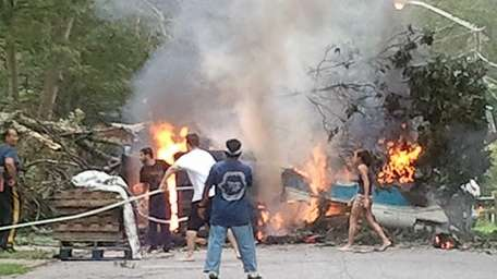 Local residents use garden hoses to extinguish the