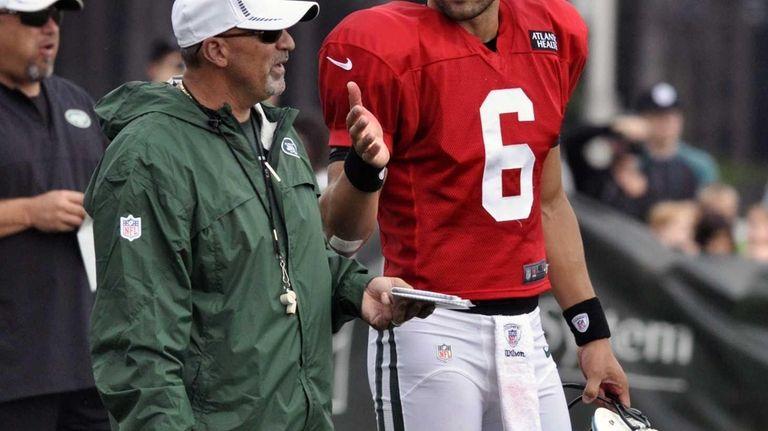 Quarterback Mark Sanchez (6) talks with offensive coordinator