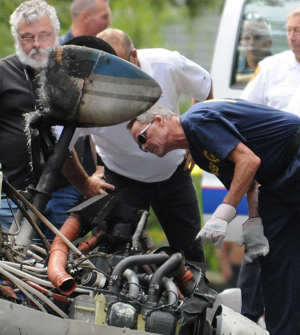NTSB investigators examine the wreckage of the single-engine
