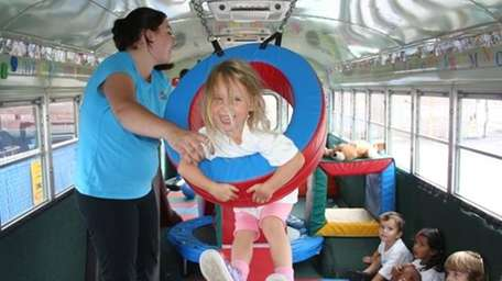 Little girl swings in a ring at a