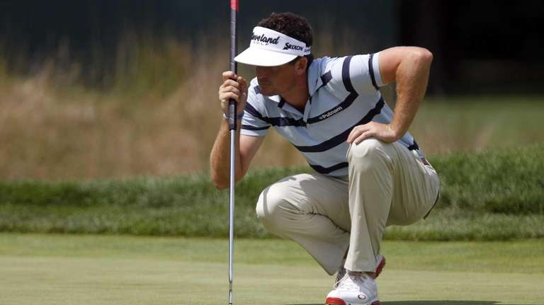 Keegan Bradley lines up a putt on the