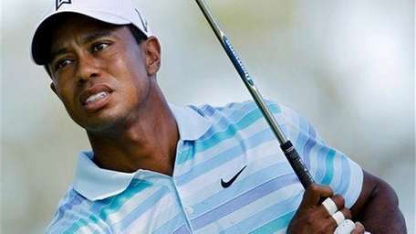 Tiger Woods follows his tee shot on the