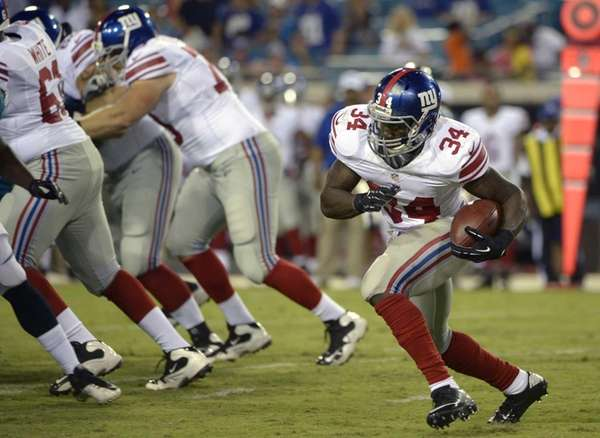 David Wilson runs around the blocking of the
