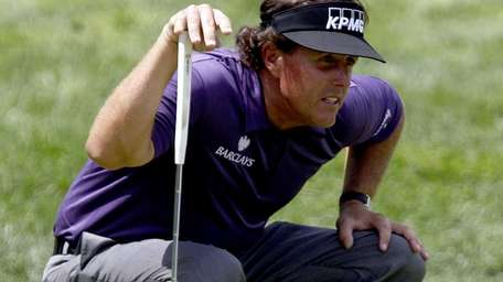 Phil Mickelson lines up a putt on the