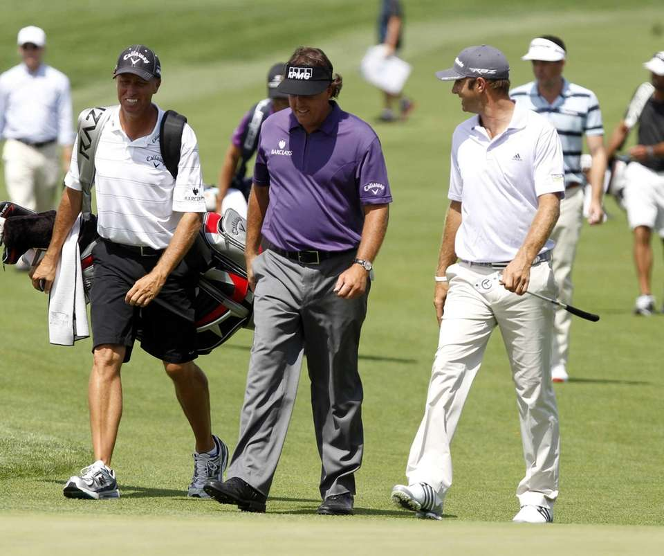 Phil Mickelson, center, and Dustin Johnson walk and