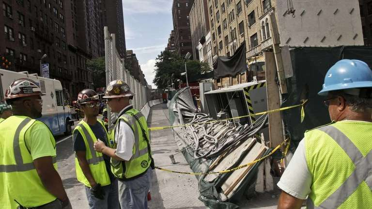 Workers examine damage following an intentional underground explosion