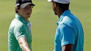 Tiger Woods shakes hands with Rory McIlroy on