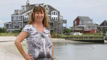 Barbara McGinn poses for a portrait beside waterfront