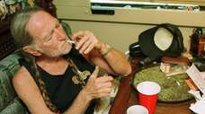 Willie Nelson takes a drag off a joint