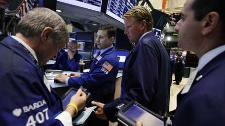 Specialist Joseph Mastrolia, center, works with traders on