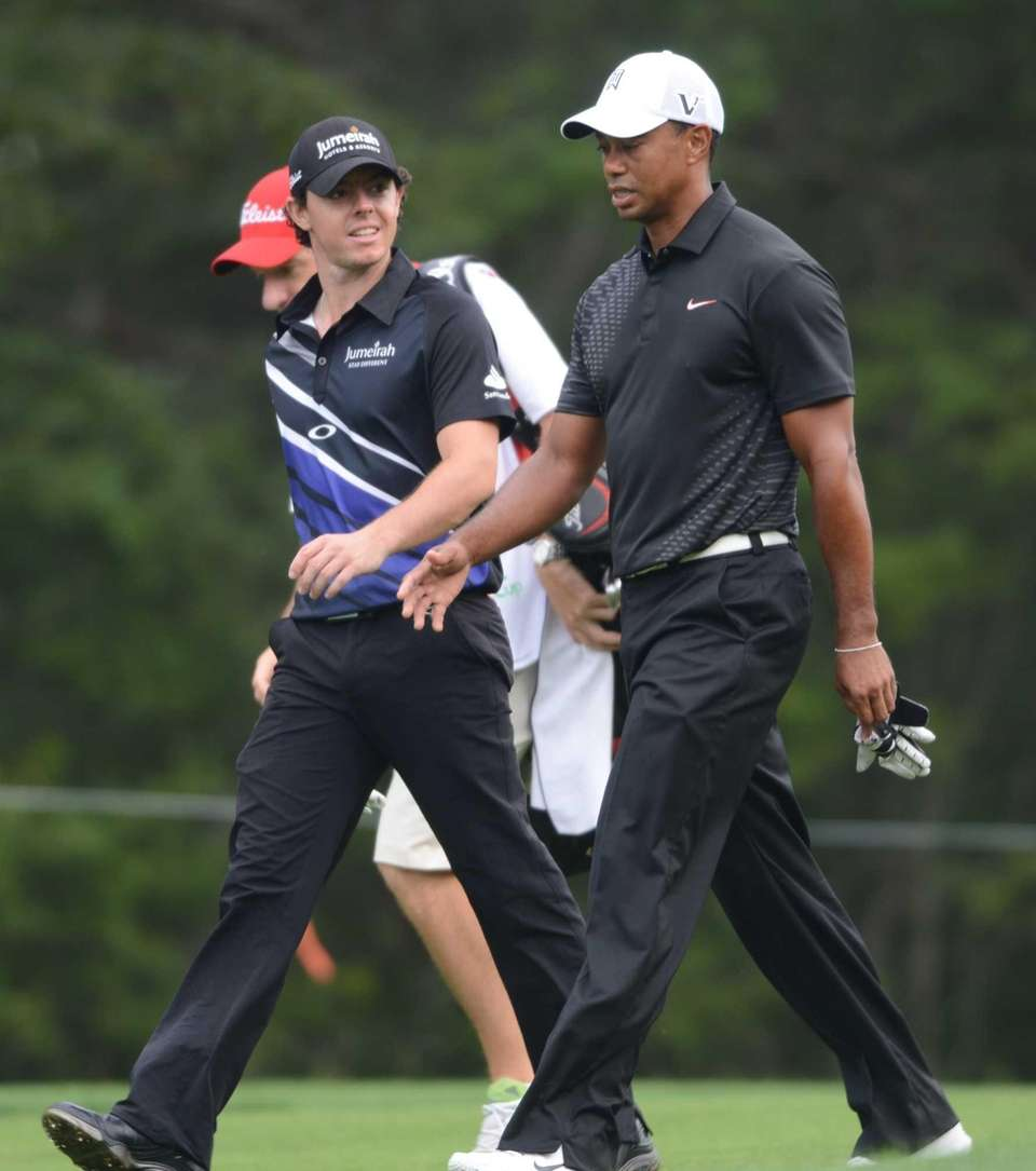 Tiger Woods, right, and Rory McIlroy walk down