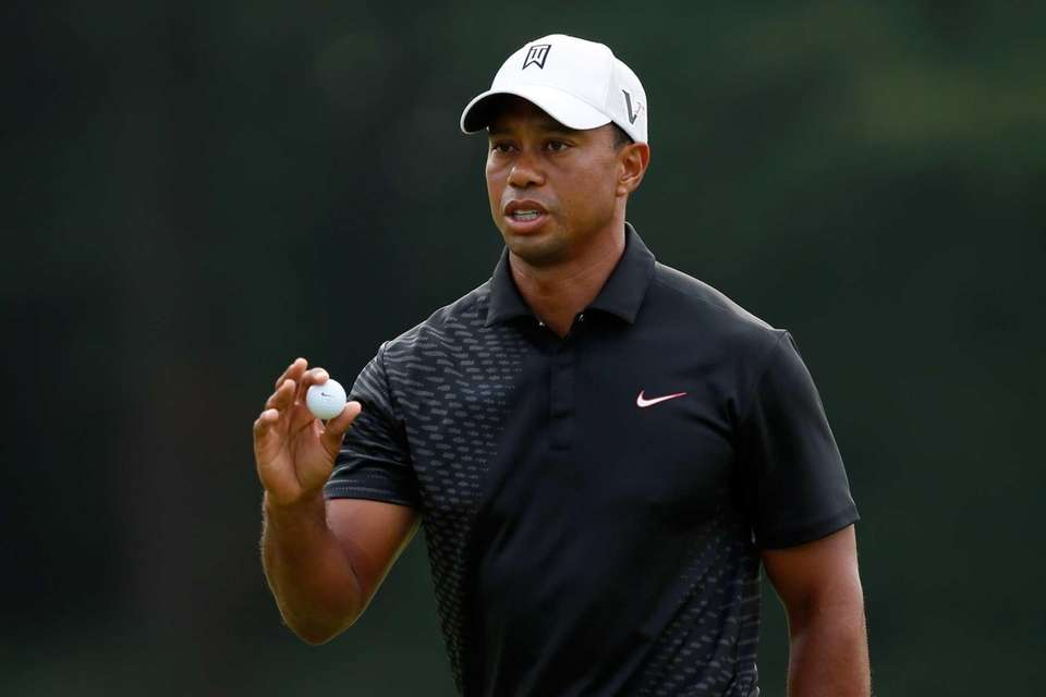 Tiger Woods reacts after he made his putt