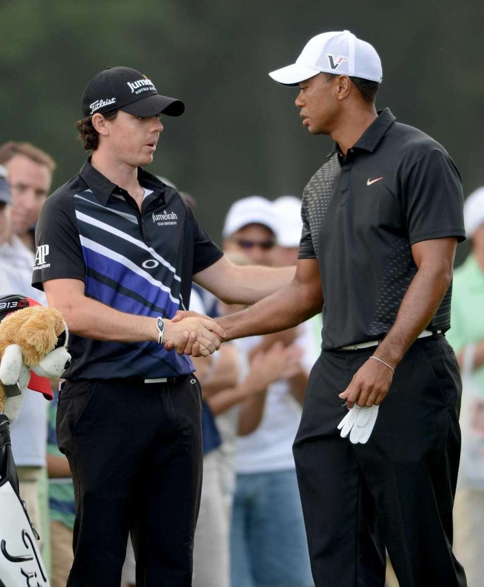 Tiger Woods, right, shakes hands with Rory McIlroy
