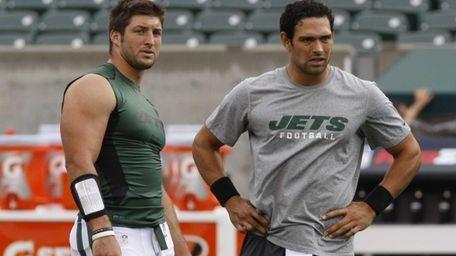 Jets quarterbacks Tim Tebow, left, and Mark Sanchez