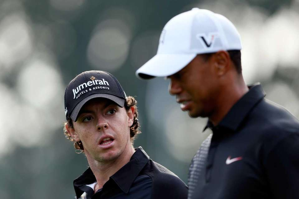 Rory McIlroy, left, and Tiger Woods talk as