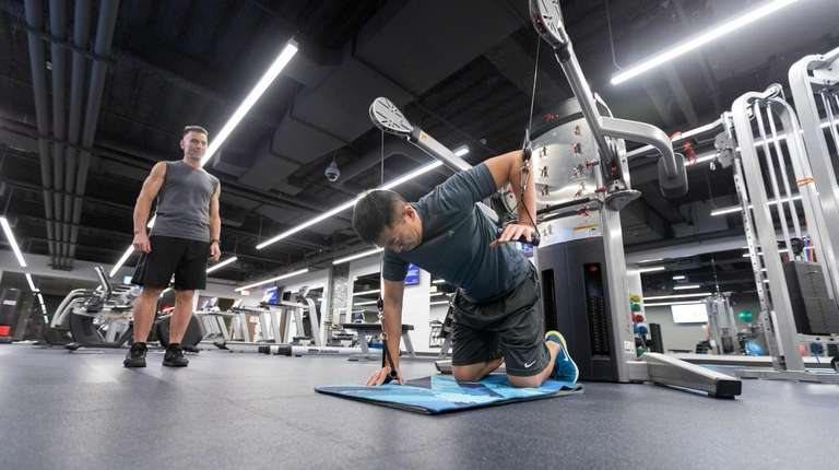 Engineer Kevin Hsu, right, works with trainer and